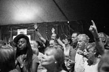 A diverse group of people standing and worshipping together in a large tent.