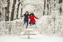 Two girls jumping off a picnic table covered in snow
