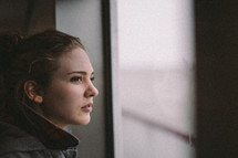 A young woman looks out of a window.
