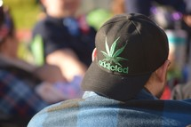 A man wearing a Marijuana leaf hat with the word addicted
