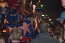 people cheering as a patriotic parade float passes by