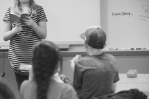 a teacher reading to her students in class