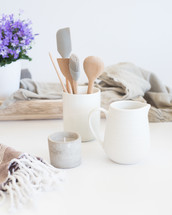 kitchen utensils, ceramic, kitchen, tools, countertop, jar, house plant, wood tray, linen fabric, votive candle, pitcher