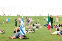 waving various flags on a grass lawn