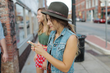 a young woman texting standing on a sidewalk with friends texting