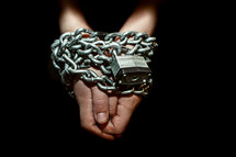 Prisoner's hands and arms chained up with lock.