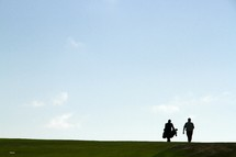 Silhouettes of two men walking along a golf course.