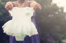 woman holding up a child's ballerina outfit