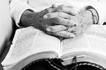 Elderly folded hands on the pages of an open Bible.