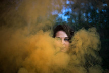 a woman standing behind smoke