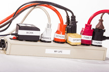 Power strip with labeled plugs depicting a busy life.
