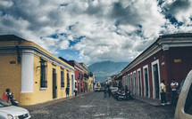 colorful buildings and parked cars along a cobble stone street in Cuba