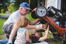 grandfather and his grandchildren fixing a lawnmower