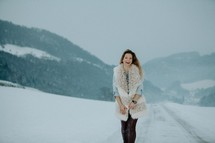 a happy woman standing in the snow