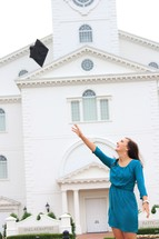 a woman tossing her graduation cap in front of a church