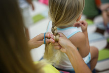 a woman braiding a girls hair