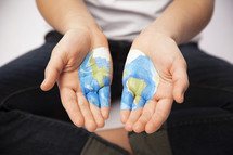 Planet Earth painted on boy's hands.