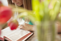 Woman reading the Bible on a wood table with tulips.