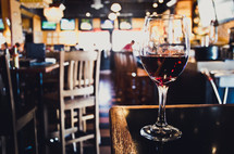 Glass of wine on the corner of a bar.