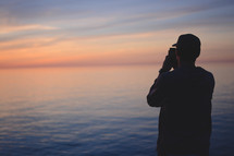 man taking a picture of the ocean at sunset