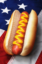 hotdog with mustard on an American flag