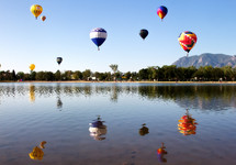 Hot air balloons  in the sky reflecting in the lake below.