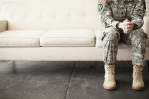 soldier sitting on a couch praying