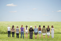 Line of women standing outside in a field holding hands.
