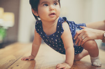 infant girl learning to crawl