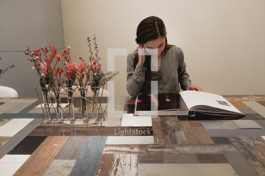 a woman looking at a book sitting along at a table