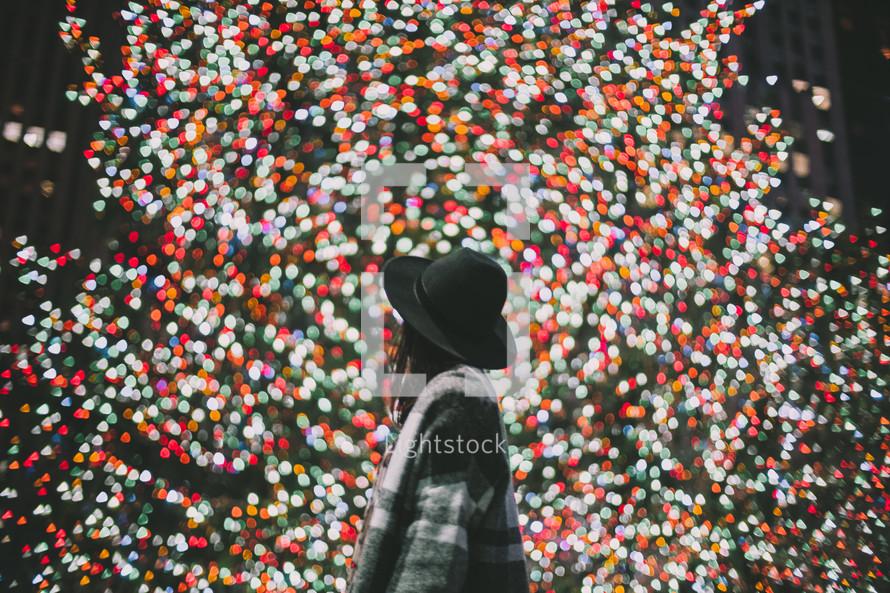 a woman looking at Christmas lights on a Christmas tree