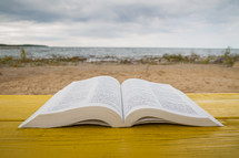 pages of an open Bible on a yellow table with beach in background
