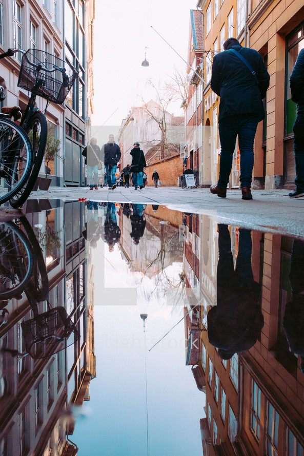 reflection in a puddle and people walking on a narrow street