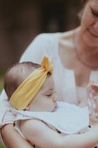 A grandmother cradling her infant granddaughter