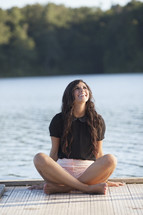 woman sitting on a dock looking up smiling
