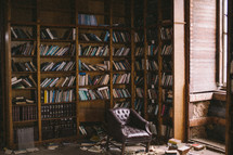 scattered books on a bookshelf and floor in a library