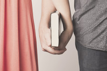 husband and wife holding a Bible together