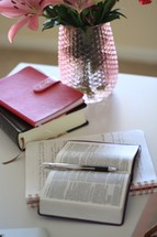 flowers in a vase and open Bible and journal on a table