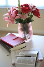 roses and lilies in a vase and notebook and Bible