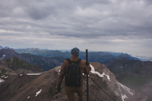 a man with a walking stick standing on a mountaintop