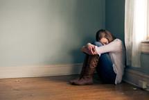 teen girl sitting alone in an empty room near a window
