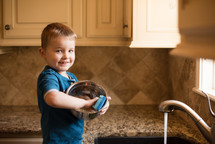 a boy washing dishes in the sink