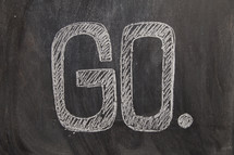 the word go written on a black chalkboard. missions concept.