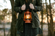 a torso of a woman holding a lantern