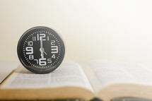 wall clock on an open Bible