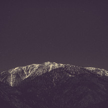 stars in a night sky over a snow covered mountain peak