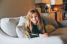 smiling girl sitting on a couch