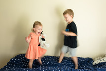 kids jumping on a bed