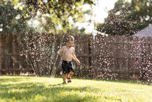 a boy playing in a sprinkler