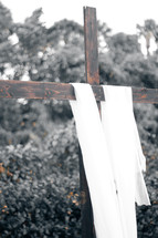 white shroud on a wooden cross